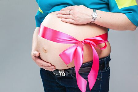 trimester: Pregnant belly with pink ribbon. Third trimester.