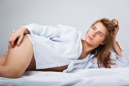 Pretty young woman in a white men's shirt. studio shot photo