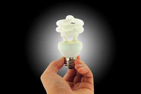 コンパクト蛍光灯電球手で開催された、黒の背景に白色のスポット ライトと分離