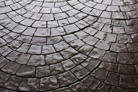 Dark rustic floor paving stones laid in a rounded pattern Stock Photo