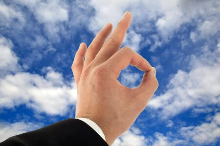 Business man's hand signing okay in the sky Stock Photo - 4920279