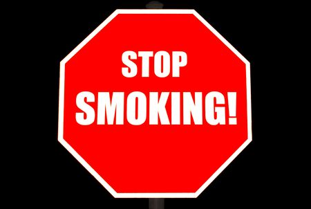 it is isolated: Bright red stop sign with STOP SMOKING on it isolated on black