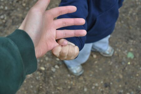 grasping: Sharp focus on a toddlers hand grasping fathers pinky Stock Photo