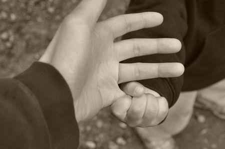 幼児の把持父の小指にクローズ アップ