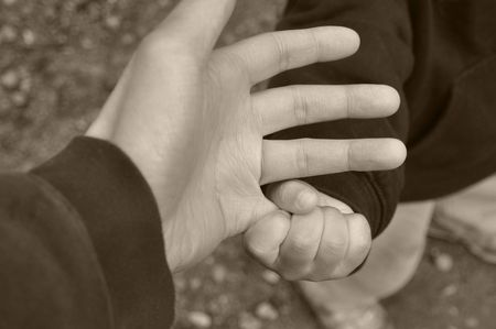 Close up on a toddler's hand grasping father's pinky