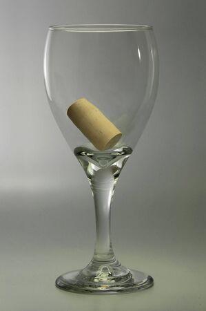 Symbolic empty wine glass containing the bottle cork