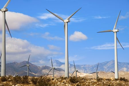 Wind turbines in a desert setting with mountains in the background Stock Photo