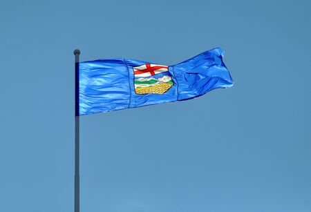 Provincial Flag for Alberta, Canada blowing in the wind illuminated by sunlight. Archivio Fotografico
