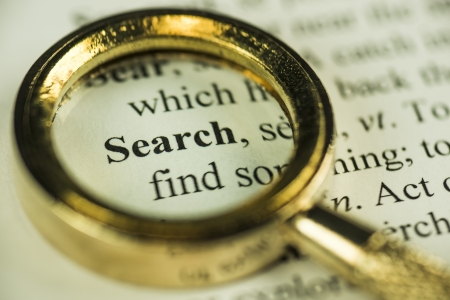 Macro Image Of A Magnifying Glass Over The Search Word In A Dictionary