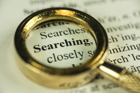 Macro Image Of A Magnifying Glass Over The Word Searching In A Dictionary