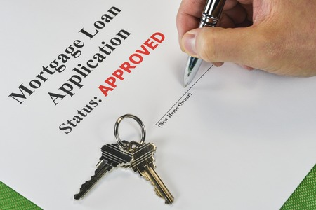homeownership: Hand Signing An Approved Real Estate Mortgage Loan Document With House Keys Stock Photo