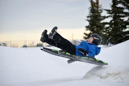 雪ランプ上の冬の楽しみの子供 SleddingTobogganing 高速