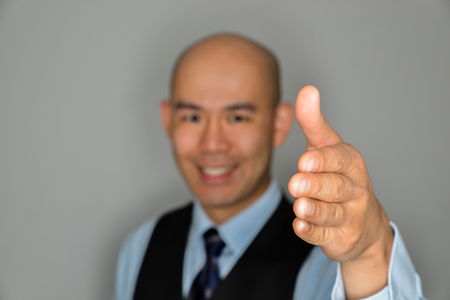 Blurred Businessman Offering Clear Handshake and Smile