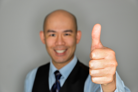 Blurred Businessman Offering Clear Thumbs Up and Smile Archivio Fotografico - 105107084
