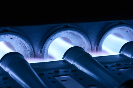 Closeup Shot Of Home Furnace Burner Ignited With Crimson Blue Flame