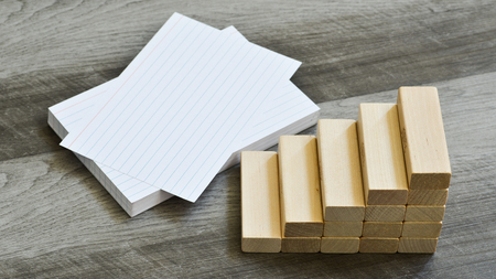 Business / Education Challenge Concept - Blank Index Cards With Stairway Upwards Of Building Blocks Over Dark Grey Wooden Background