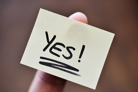Success / Goal Concept - Index Finger Holding Note With Handwritten YES Word