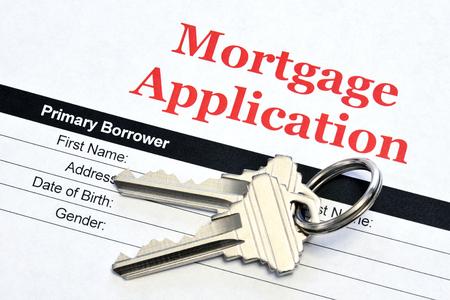 Documento de préstamo de solicitud de hipoteca inmobiliaria con llaves de casa