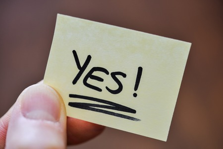 Success / Goal Concept - Fingers Holding Note With Handwritten YES Word