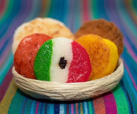 basket with a bunch of typical mexican coconut candies honey cocada traditional mexican flag carpet background isolated colors sarape mexican