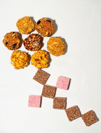 flower made with bunch of typical mexican seeds candies nuts peanuts honey amaranth pink brown chocolate white background isolated