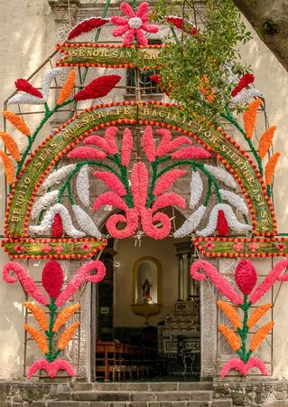 ancient catholic church entry door mexico flower decoration green old tree blue sky no people front view