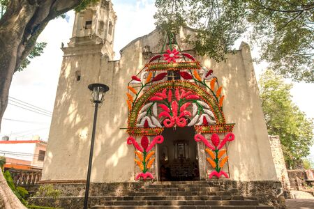 ancient catholic church mexico flower decoration green old tree blue sky no people front view