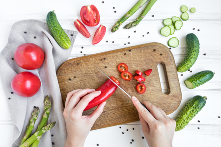 Woman hands slicing sweet pepper on wooden cutting board, surrounded by vegetables and eggs. Home cooking concept. Salad or any vegetarian dish. Flat lay, top view Stock Photo