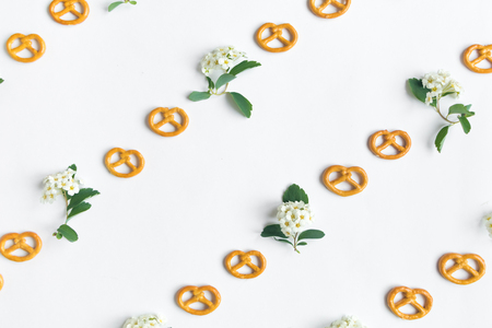 Minimalistic diagonal cookies pretzels and spirea arguta flowers pattern on white background. Flat lay, top view, diagonal lines pattern