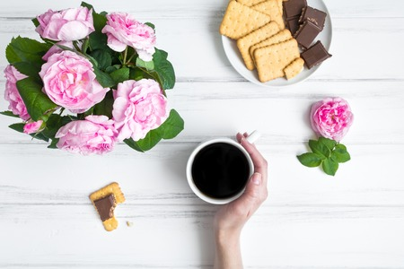 romantic places: Composition with cup of coffee, crackers, chocolate and rose flowers against white vintage wooden table. Cozy home morning composition. Sketching or writing and drinking coffee. Flat lay, top view Stock Photo