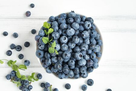 bawl: Fresh blueberries with mint branches in white bawl on white wooden table. Flat lay, top view Stock Photo