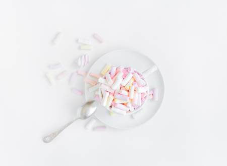 clutter: Colorful light marshmallows in a white cup with a spoon on white background. Light soft composition, sweet food concept. Top view, flat lay