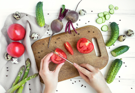 Woman hands slicing tomato on wooden cutting board, surrounded by vegetables and eggs. Home cooking concept. Salad or any vegetarian dish. Flat lay, top view Archivio Fotografico