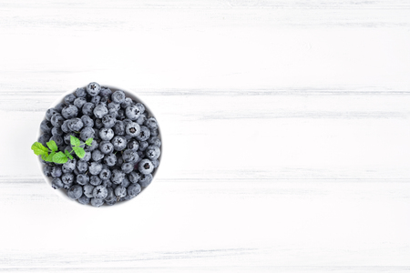 Fresh blueberries with a mint branch in white bawl on white wooden table. Flat lay, top view