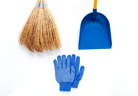 Minimalist cleaning colorful composition on white background. Blue fabric gloves, broom and scoop. Flat lay, view from above, place for your text Фото со стока