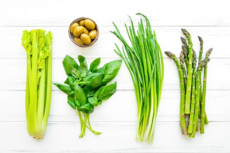 Green fresh herbs and vegetables on white wooden background. Flat lay, eco vegan background with celery, basil leaves, onions, olives and asparagus. View from above Stock Photo