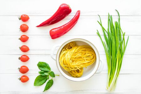 Ingredients for healthy Italian pasta with herbs and vegetables or salad, bright background. Pasta nests in a pan, onions, tomatos, sweet pepper, basil leaves. Flat lay, view from above