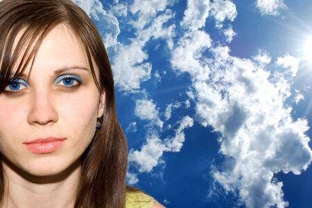 The beautiful girl against dark blue and colourful clouds photo