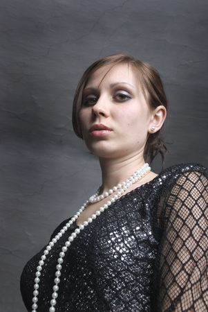 The young woman in black beautiful dress, on neck beads from pearls
