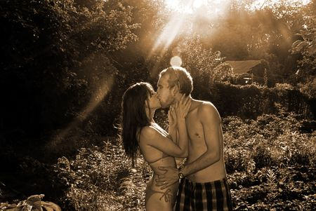 Young pair in garden, passionate kisses and warm embraces