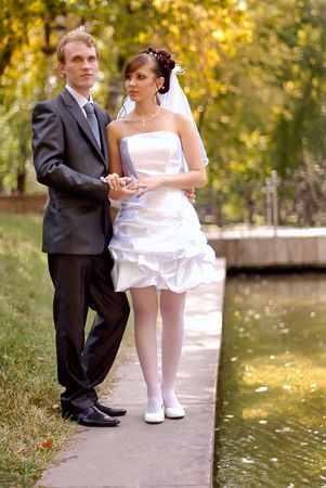 The bride and groom, standing near the lake in the park on a beautiful sunny day photo