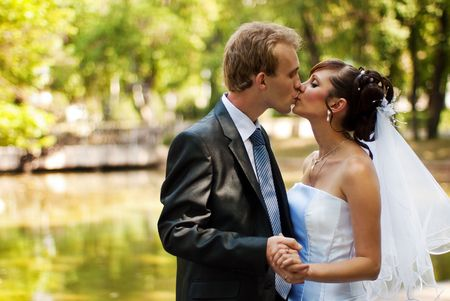 Newlyweds kissing in a park, holding hands