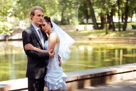 Young bride and groom embracing, standing in a park on a beautiful sunny day