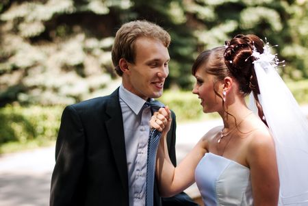 neckties: Beautiful and young married couple in the park, wife caught her husband for a tie Stock Photo