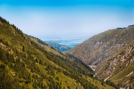 The national nature of Kazakhstan. Height of 2500 meters. Mountain peaks, green forests, rugged mountains and blue sky and fresh air.
