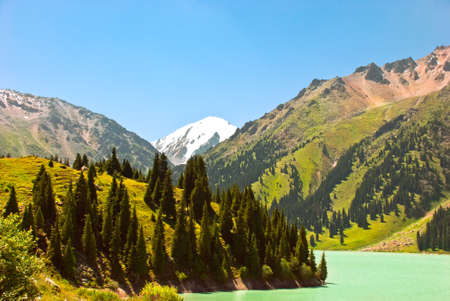 The big lake located highly in mountains among coniferous wood. photo