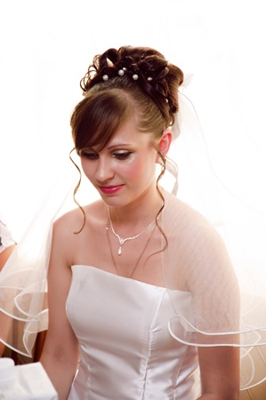 A beautiful portrait of a young bride in a white dress. photo