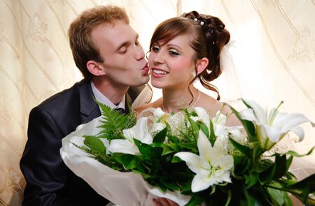 Portrait of a young and beautiful married, the groom kisses the bride. photo