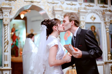 The bride and groom kiss at the ceremony in the church. photo