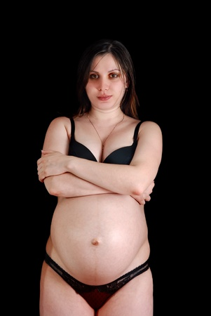 The stomach of the pregnant woman is embraced by hands.